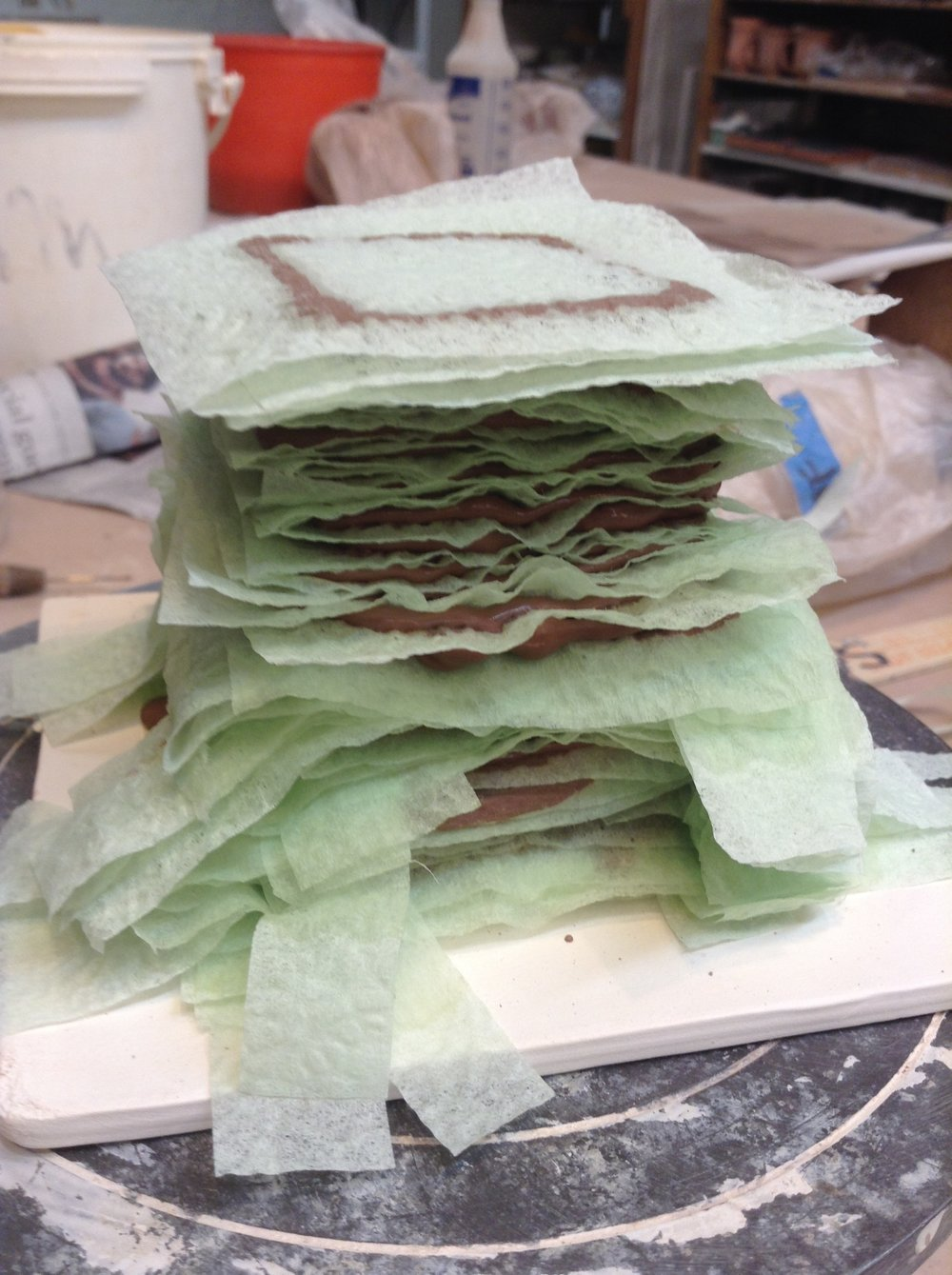 Several inches of the stacked form showing the change from napkin strips to napkin squares. The ultimate choice will be solid squares, unless there is some structure also being formed inside the form.