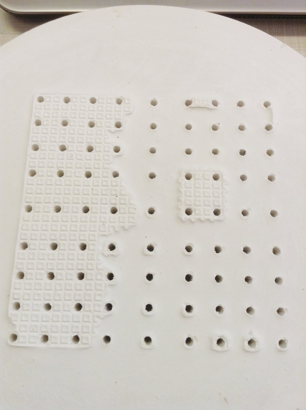 Square array made of plaster. Holes are about 1/2 inch deep to accept rod material.