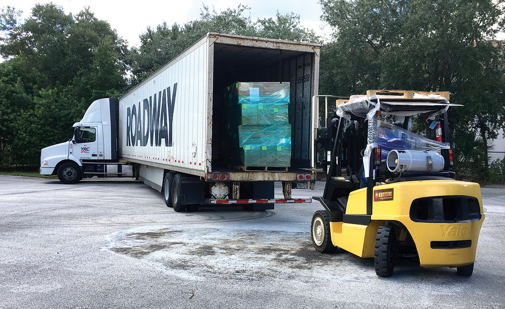 Shoeboxes arrive in Orlando, and then are cased prior to being loaded on a cargo container for shipment to Haiti.