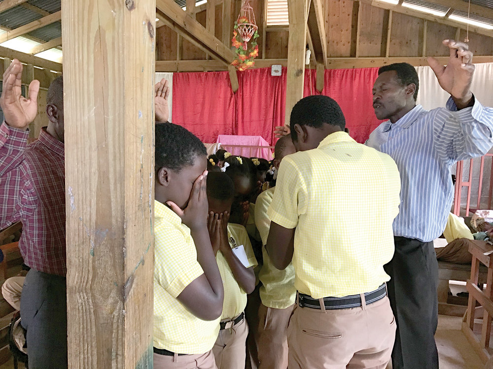 Students from the New Missions Christian Academy in Tom Gateau pray to make Jesus Lord of their lives.