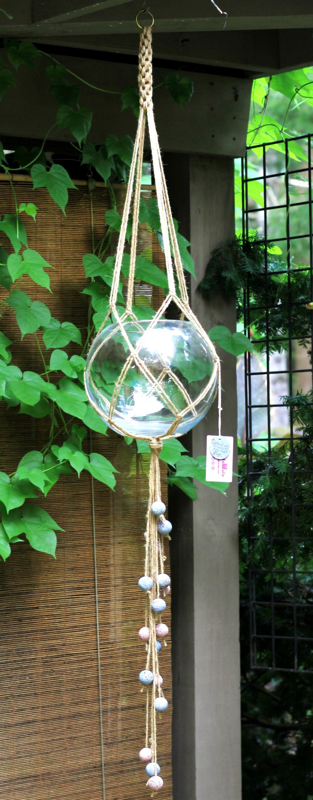 Terrarium or fish bowl in a jute macramé hanger w/ hypertufa beads.