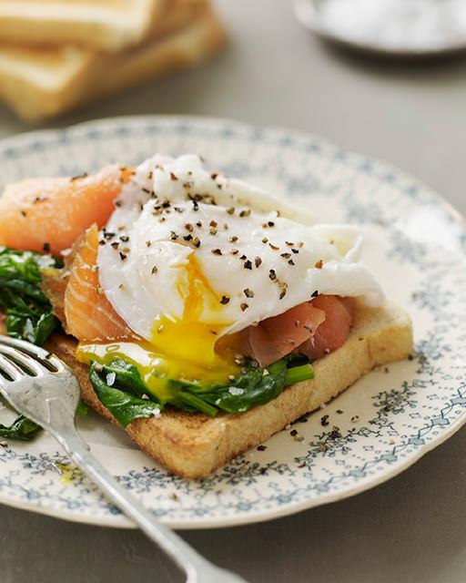 This smoked salmon version uses bread as the base and adds a layer of spinach to break up the fatty goodness of the smoked salmon + egg.