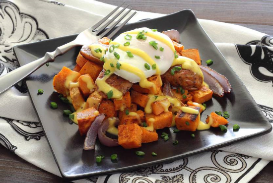 Paleo Eggs Benedict puts a poached egg on top of sausages + sweet potato hash (plus a paleo hollandaise)
