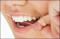 Zahnzwischenräume mit Zahnseide reinigen