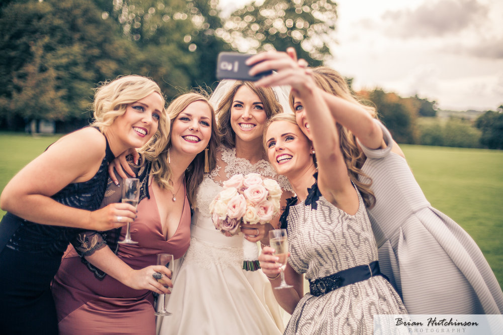 Bride and bridesmaid take a fun photograph