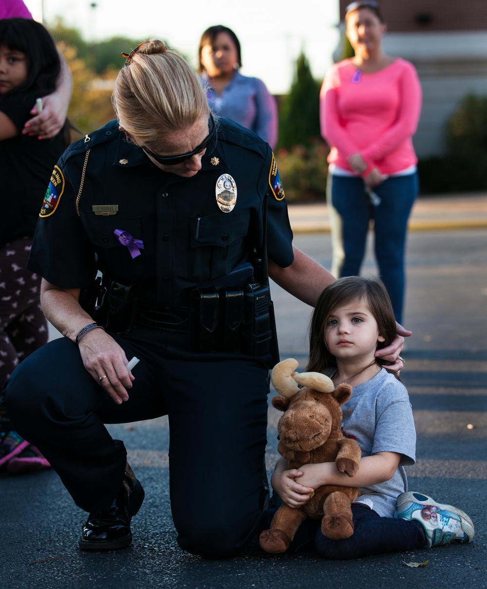 Women and men, young and old, gathered in the parking lot in front of the Justice Center in Bowling Green, Kentucky, to attend a candlelight vigil for awareness of domestic violence. This event was a part of the Domestic Violence Awareness Month that occurred on Thursday, October 15, 2015. One of the participants, Officer Penny Bowles, looked after, Allyson Trowbridge, 4, the daughter of an abused woman who attended the event.