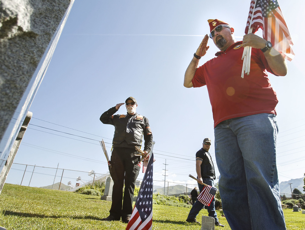 Marine Corps League member and veteran, Brian Nicholes, right, and Ron Woodward salute a grave of a fallen American soldier at Mt Olivet Cemetery in Salt Lake City on Saturday, May 28, 2016.