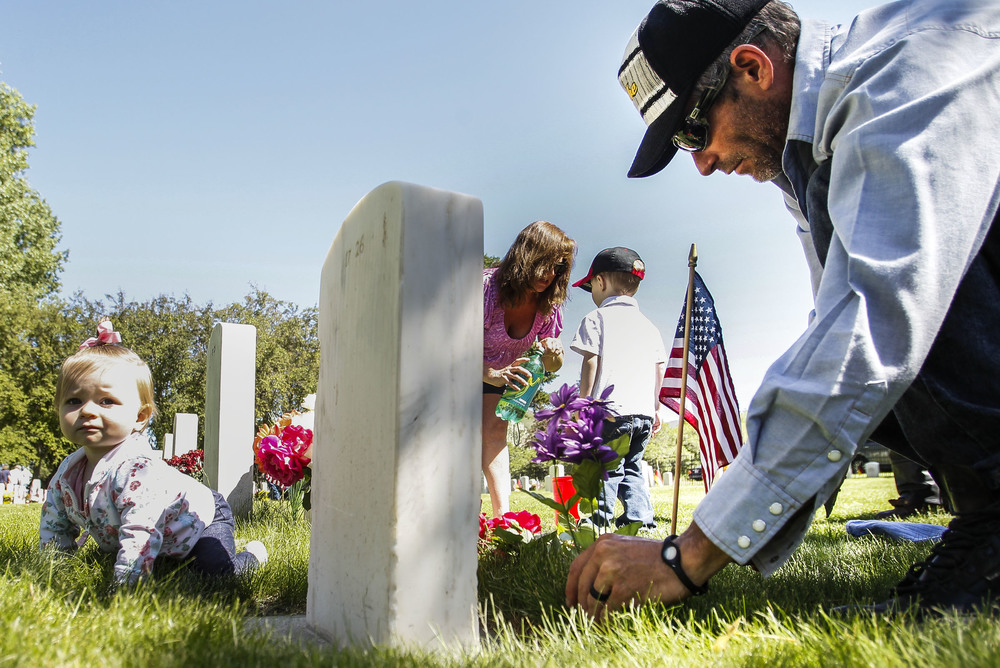Arley Sheldon, right, and his family visited deceased family members at the Memorial Day March and Ceremony that was held at Fort Douglas Cemetery in Salt Lake City, Utah, on Monday, May 30, 2016.