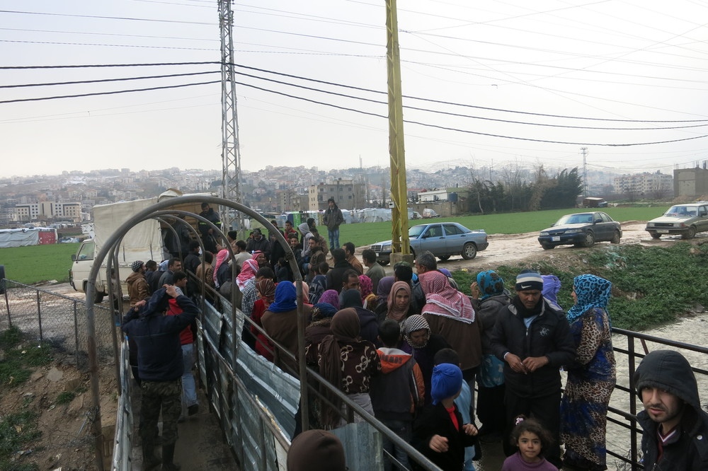 Refugees line up in Lebanon to receive packages full of life saving aid.