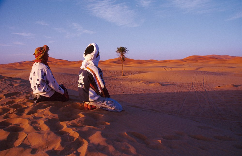 Bedouin Muslim's in North Africa kneel in the desert.