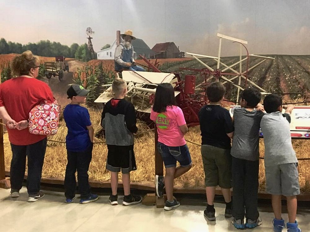 A group of students visit an interactive diorama at Bayer Museum Of Agriculture from Sundown ISD. Here's one class listening to Cyrus McCormick telling about the invention of the reaper.