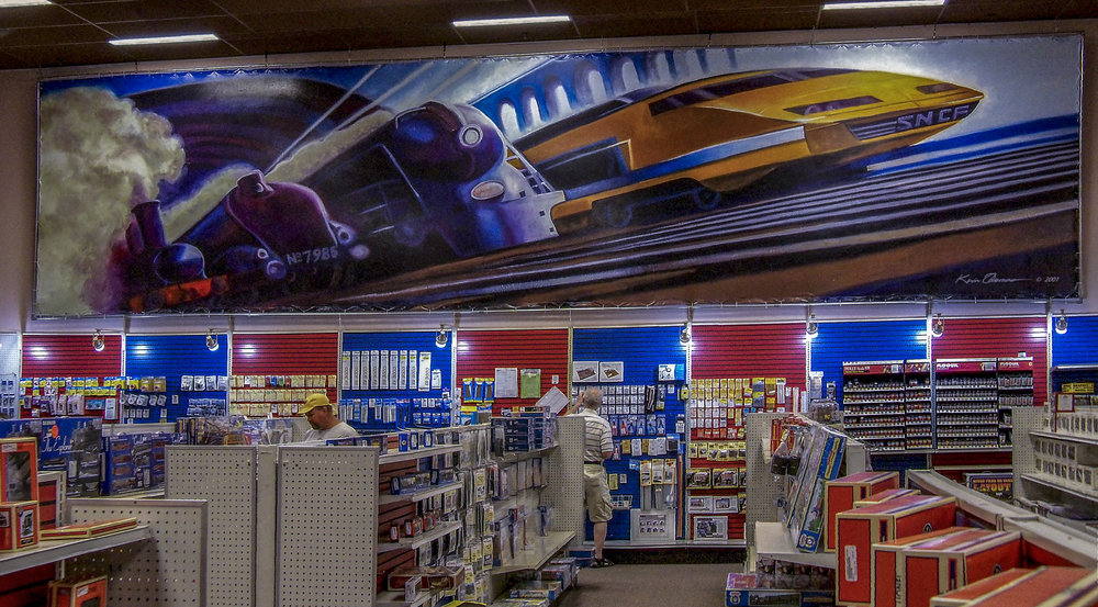 """""""Trains"""" mural installed • 12' x 35' • One of three different hand painted mural-backdrops for the franchise • HobbyTown USA, Kennesaw, GA  © KT"""