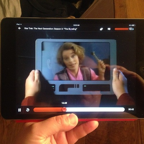 "Figure 2: Picture in picture. A photograph of me on a lonely work trip, far from home, holding an iPad and watching a scene from Star Trek The Next Generation Season 3 episode, ""The Bonding."" In the scene, a child holds an uncannily similar touchscreen device and watches home movies because he misses home."