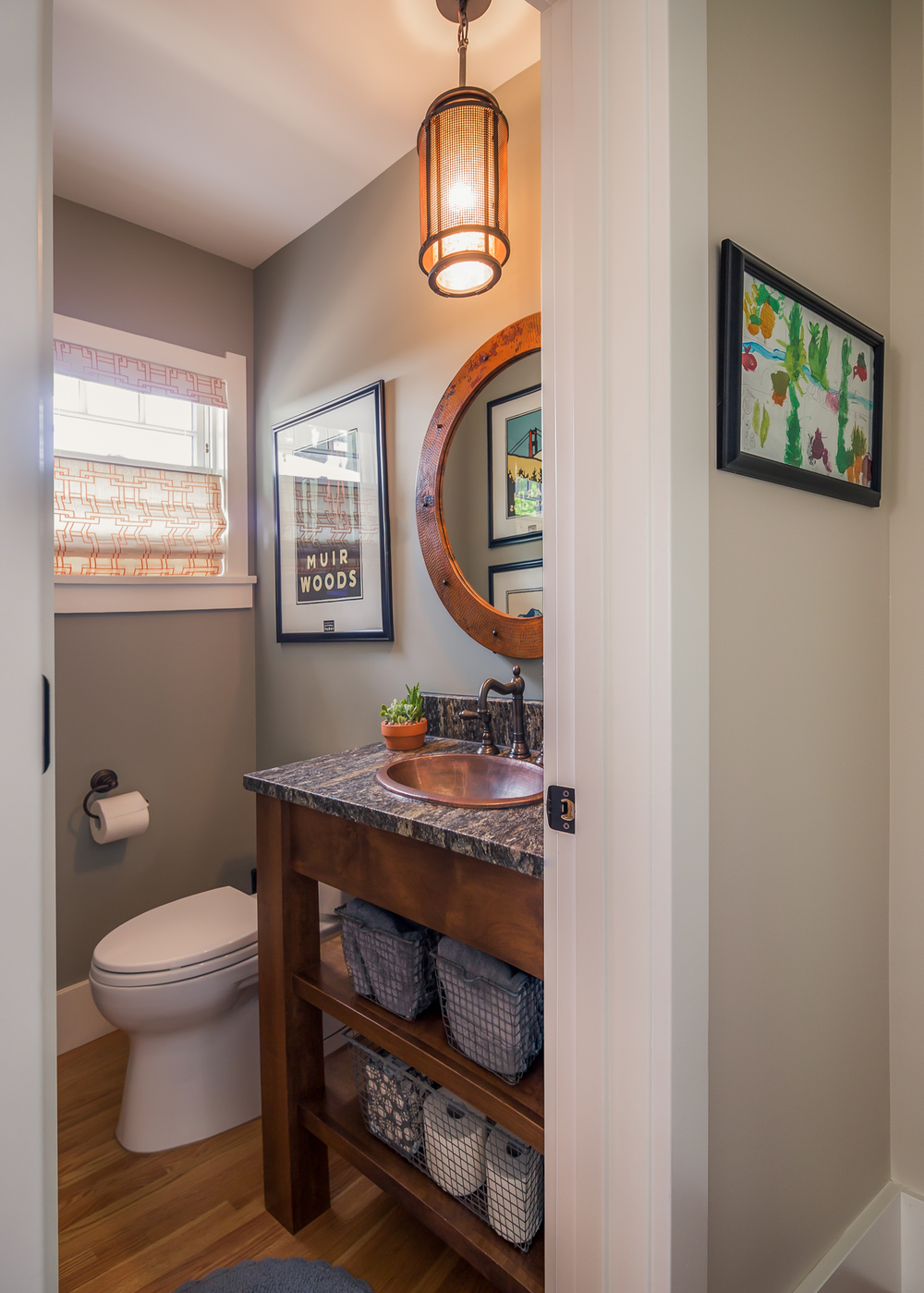 The first floor powder room has a custom vanity, copper sink, mirror and custom roman blind.