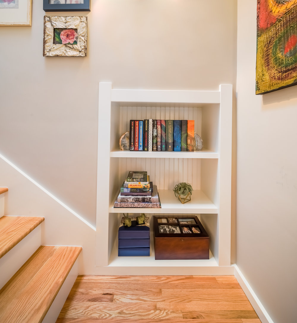 We had the space to add a little bookshelf on the stair's landing.  I had the trim match the rest of the home and added beadboard to the back for interest.