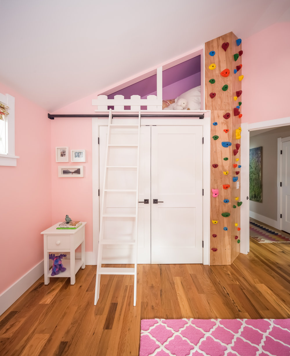This is a great example of what to do with the space above a closet in a room with a vaulted ceiling!  The client's daughter loves the climbing wall and the reading nook.  The ladder slides to the side when not in use.