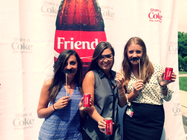 """Three women with funny photo props holding Coca-Cola cans in front of a Coca-Cola backdrop to promote the """"Share a Coke"""" marketing campaign"""
