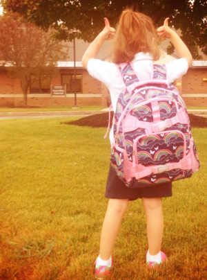 Young girl wearing a new backpack holding two thumbs up.