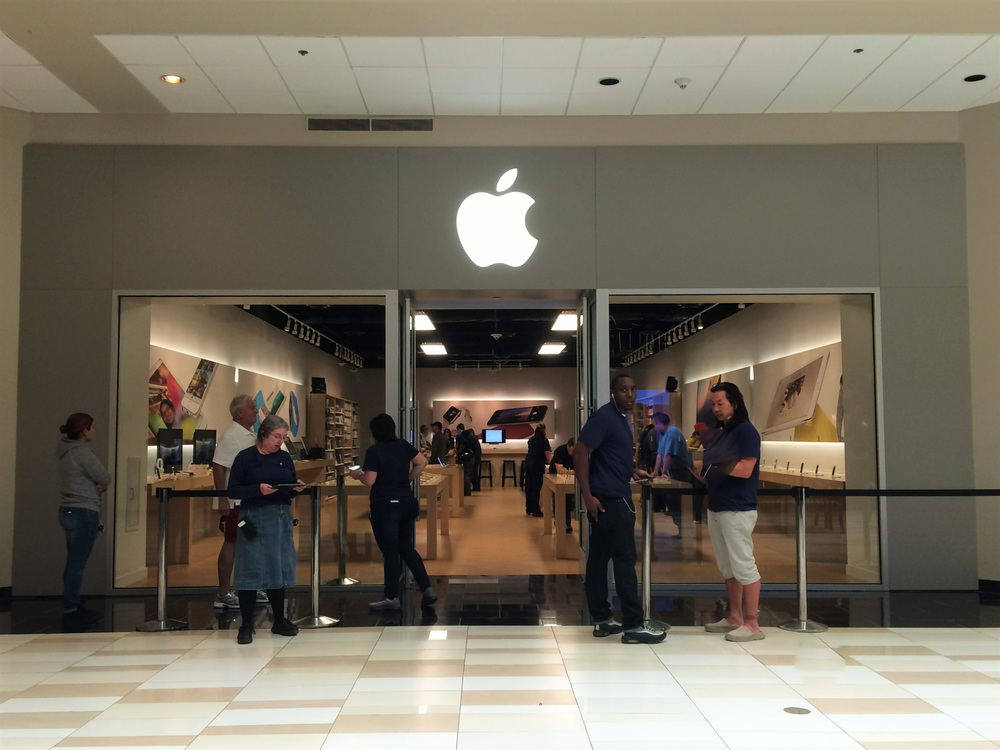Apple storefront with four Apple employees standing in front.