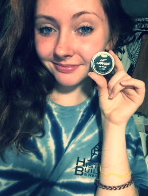 Young woman holding a Lush product to demonstrate brand loyalty