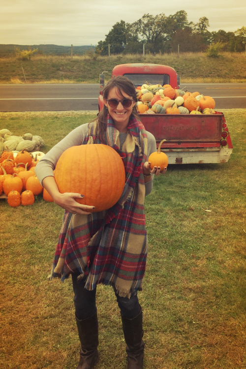 Megan Finin, senior marketing strategist at Sparkshoppe, holding one very large pumpkin and one very small pumpkin