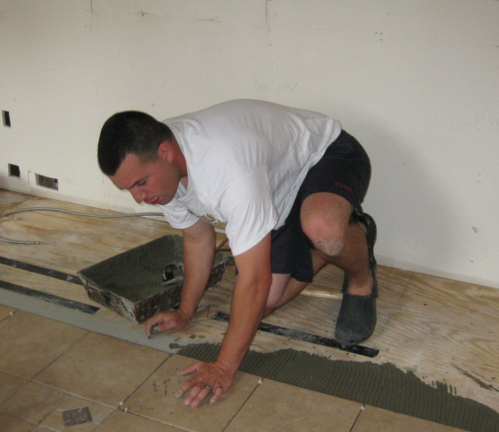 Young man installing tile and grout as part of a DIY project