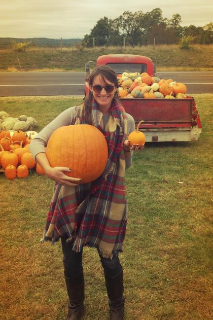 Senior marketing strategist Megan Finin holding one large pumpkin and one small pumpkin