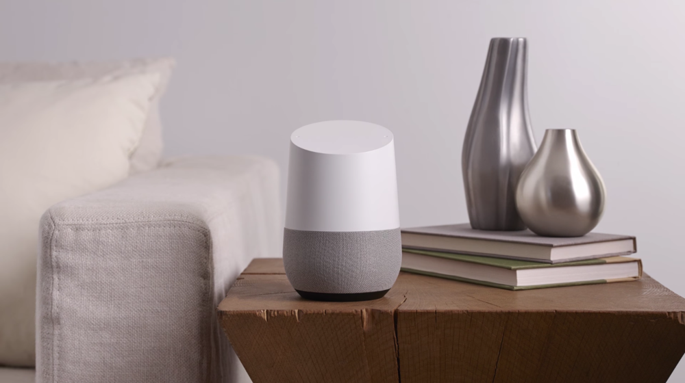 A Google Home device on a living room end table in front of two books and decor.