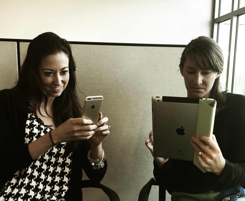 Sparkshoppe digital marketing team members Maritza and Megan browsing social media on their mobile devices