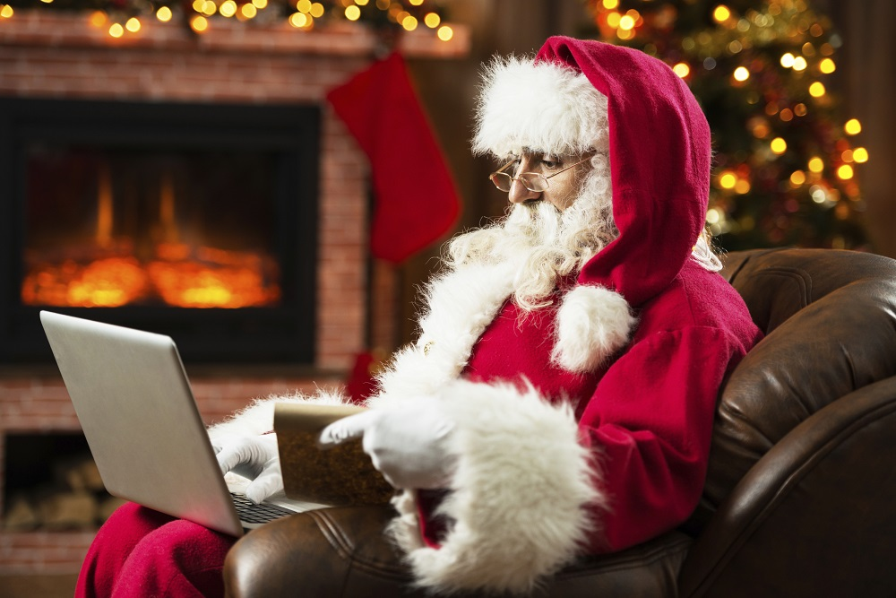 Santa Claus shopping online with a list