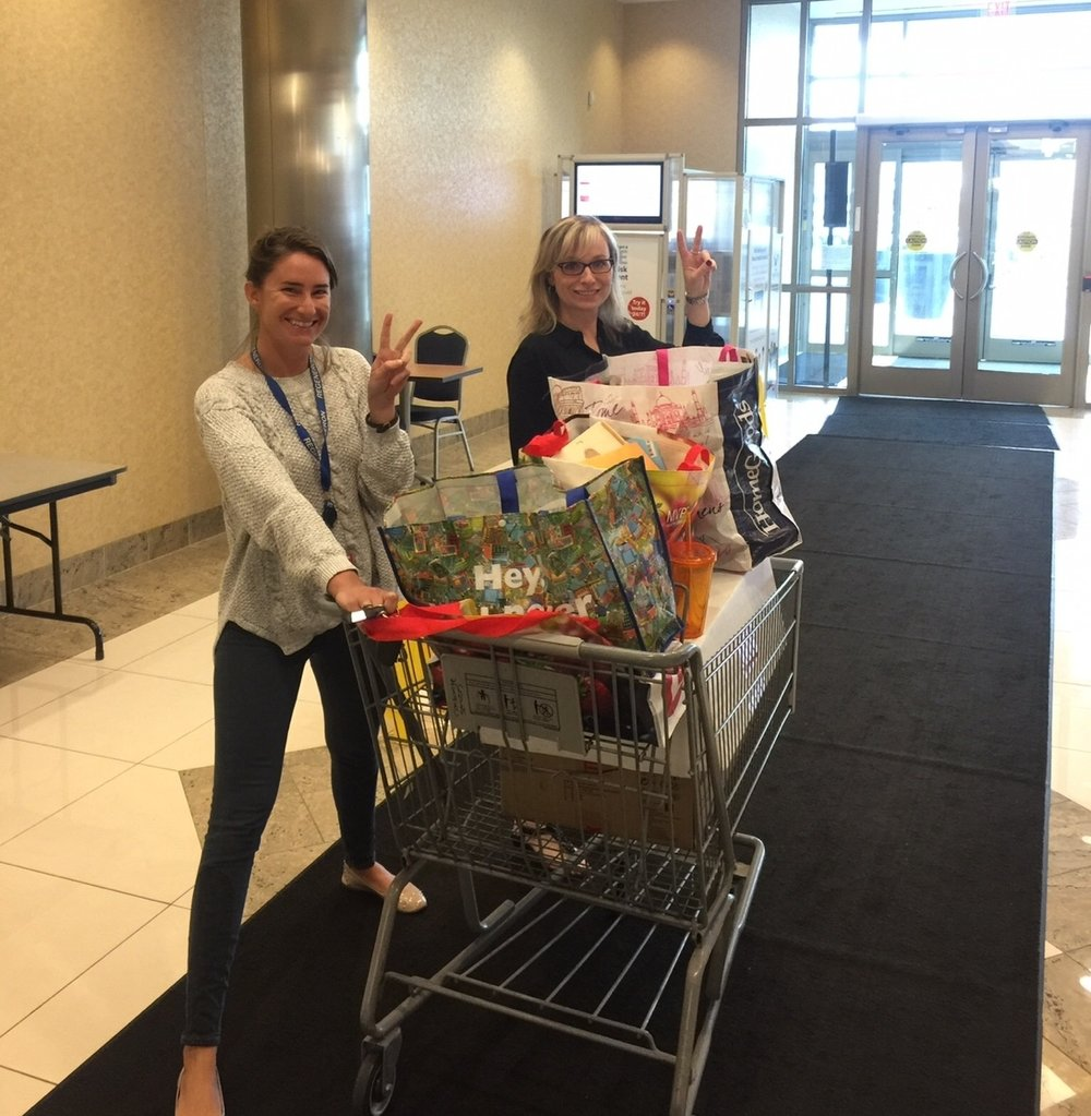 Shopper marketing experts Megan Finin and Heidi Reale with a shopping cart full of Consumer Packaged Goods.