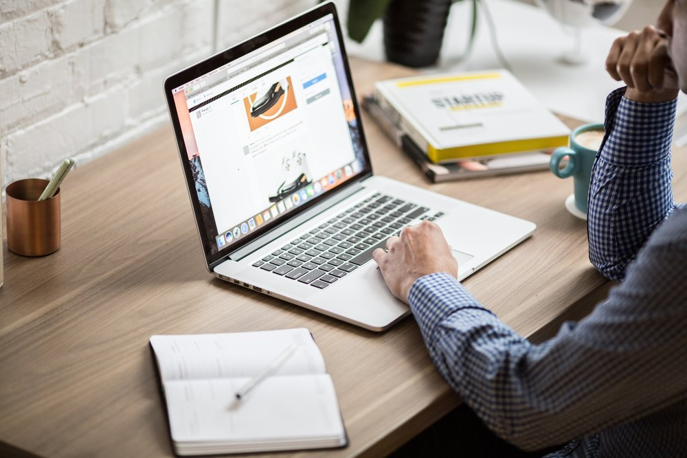Person sitting at a computer desk shopping online next to open notebooks.