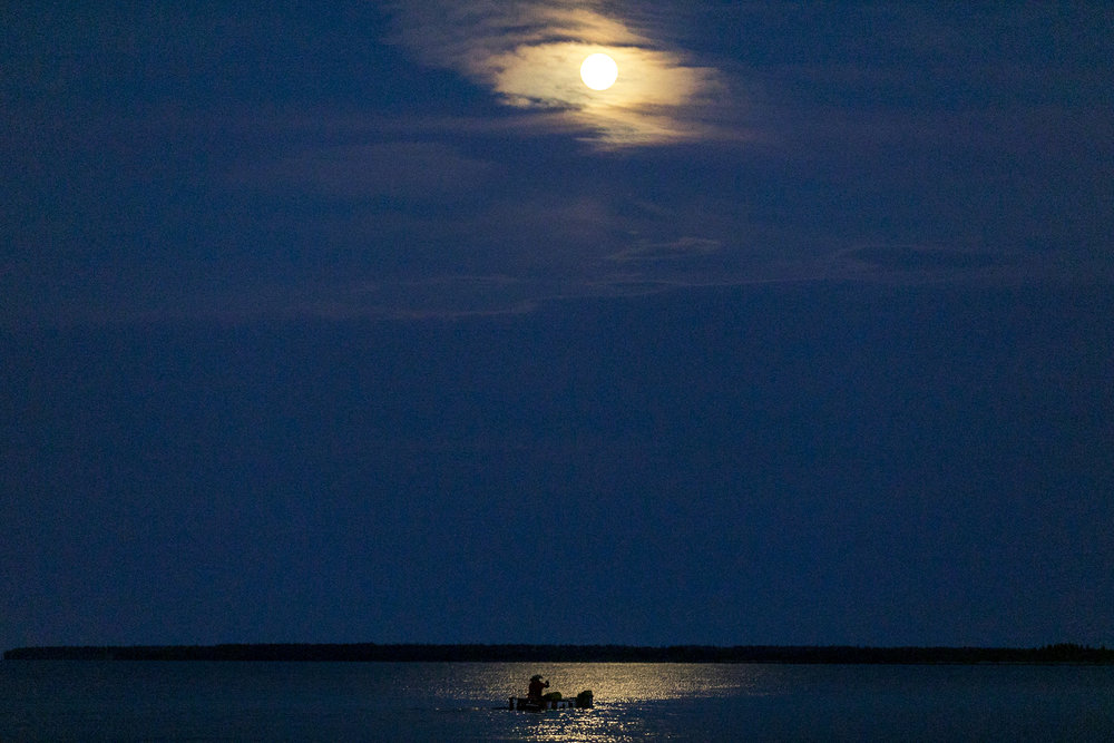 Mike Ranta portages a point of land and paddles a full day with storms circulating. By night fall, the winds subsided and ranta pushed on under a full moon on Lake Winnipeg, Manitoba. 20170709.  Photo/David Jackson