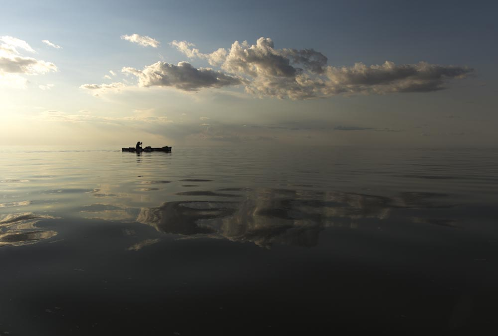 Meeting a few big fans on the water and adding under calm skies and reflective water, Mike Rata paddles all day and becomes wind bound by night fall on Lake Winnipeg, Manitoba. 20170804.  Photo/David Jackson