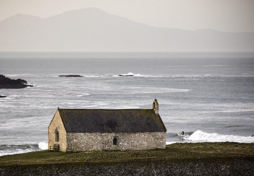 Branywen Hughes surfs with locals at the secret spot near the church, Wales, United Kingdom. Photo/ David Jackson