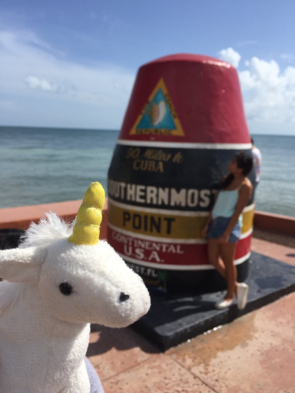 Opal the Unicorn visits the Southernmost point of the United States, where the line to get a solo photo was so long, she decided it was best to forego the queue all together and include a stranger in her selfie.