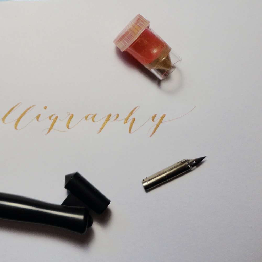 Tools used in Calligraphy for this post: Speedball Oblique Pen Holder, D. Leonardt and Co. EF Principle Nib, Ink mixture of Finetec Arabic Gold, Rose Watercolor, Water, and Gum Arabic, in a Dinky Dip. Ink shown has settled and separated, however once mixed, holds a cohesive consistency.