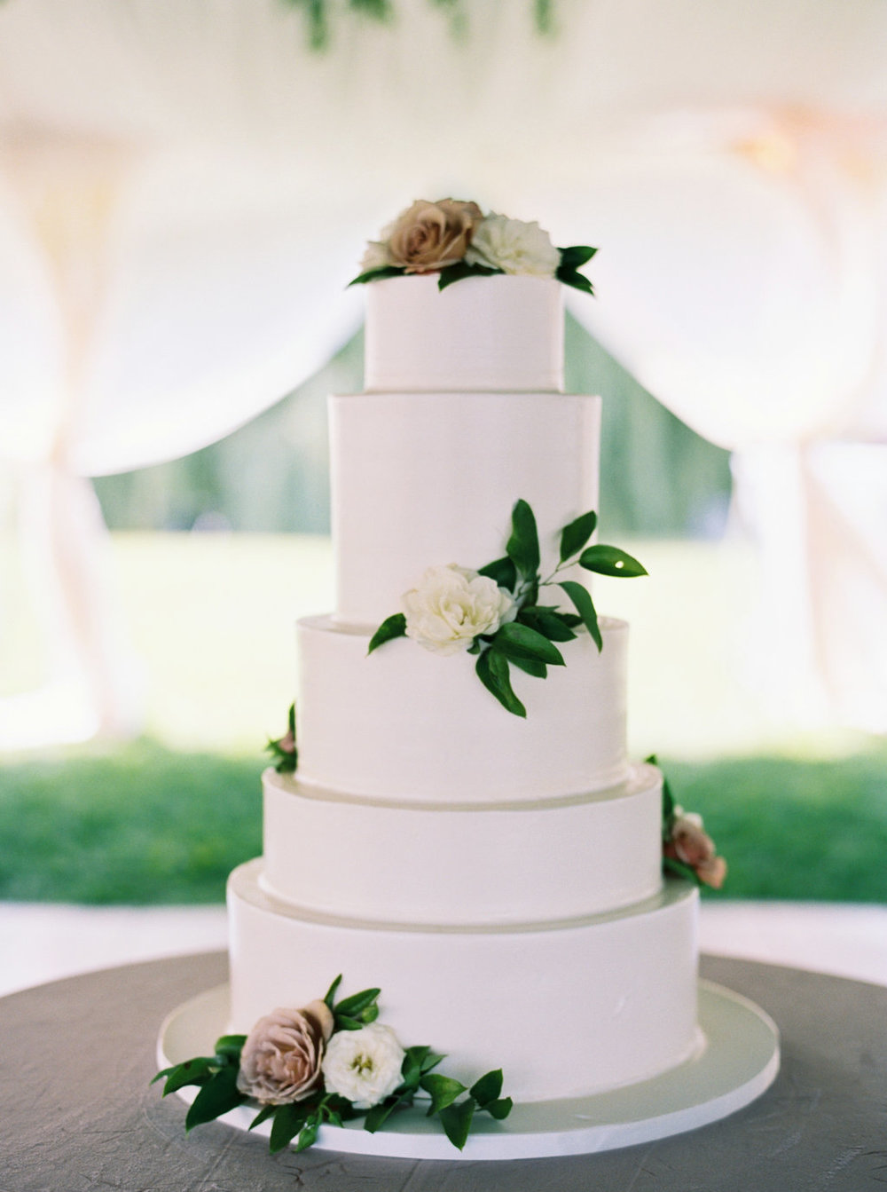 Simple white, tiered wedding cake with fresh flowers.