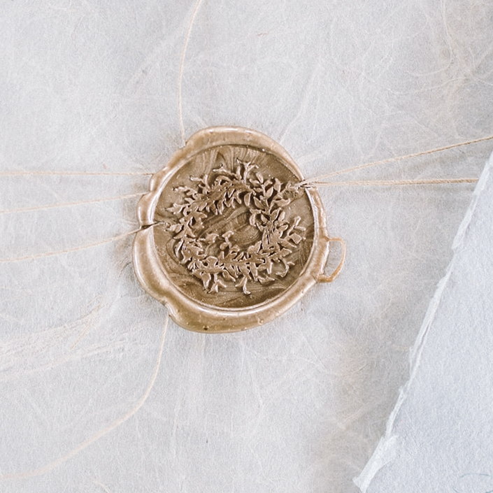 Ivy wreath wax seal in gold for wedding invitations.