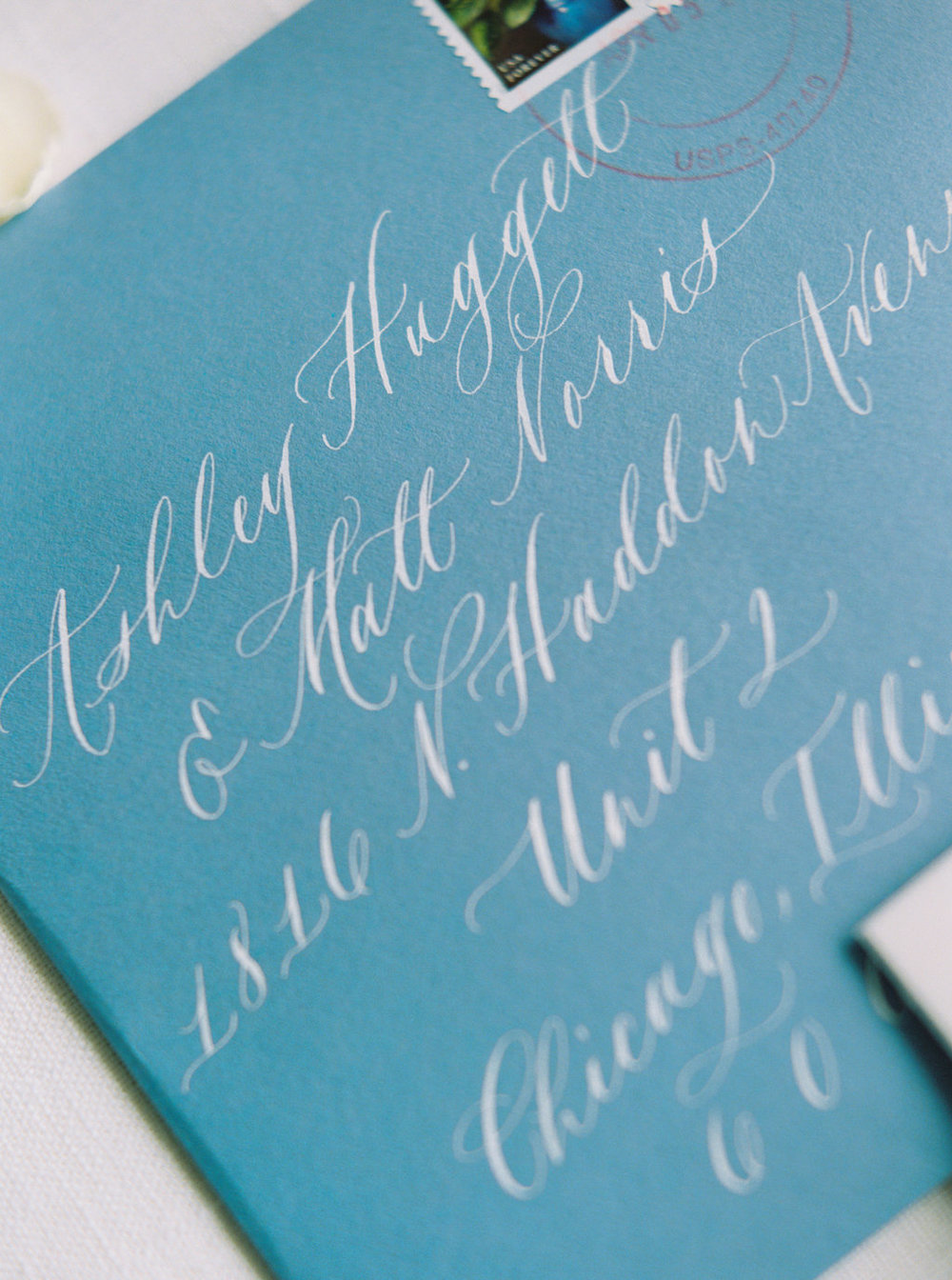 Square blue envelopes with white calligraphy for a Northern Michigan custom wedding invitation suite.