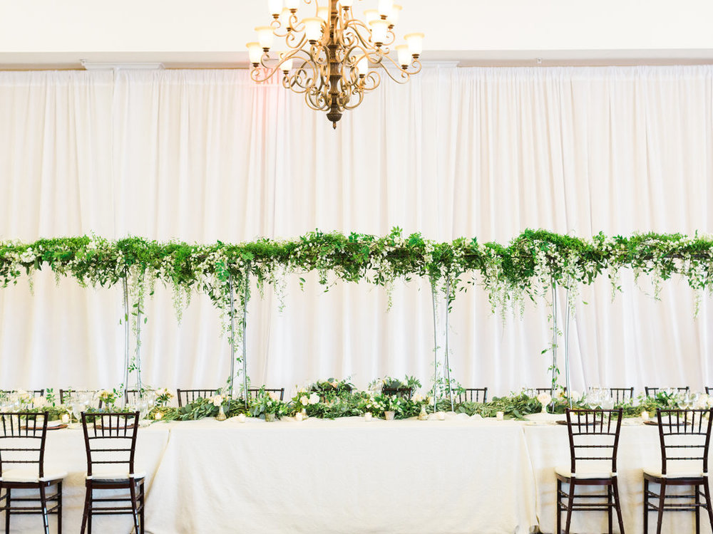 Greenery and table decor for head table at a Bay Harbor Yacht Club wedding.