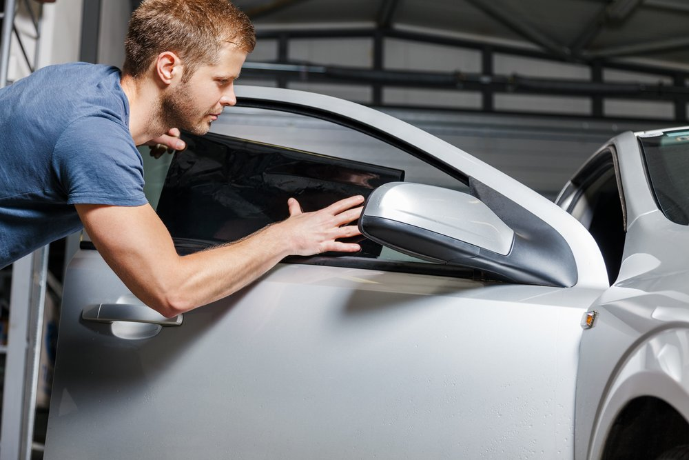 man-applying-window-tint-to-car