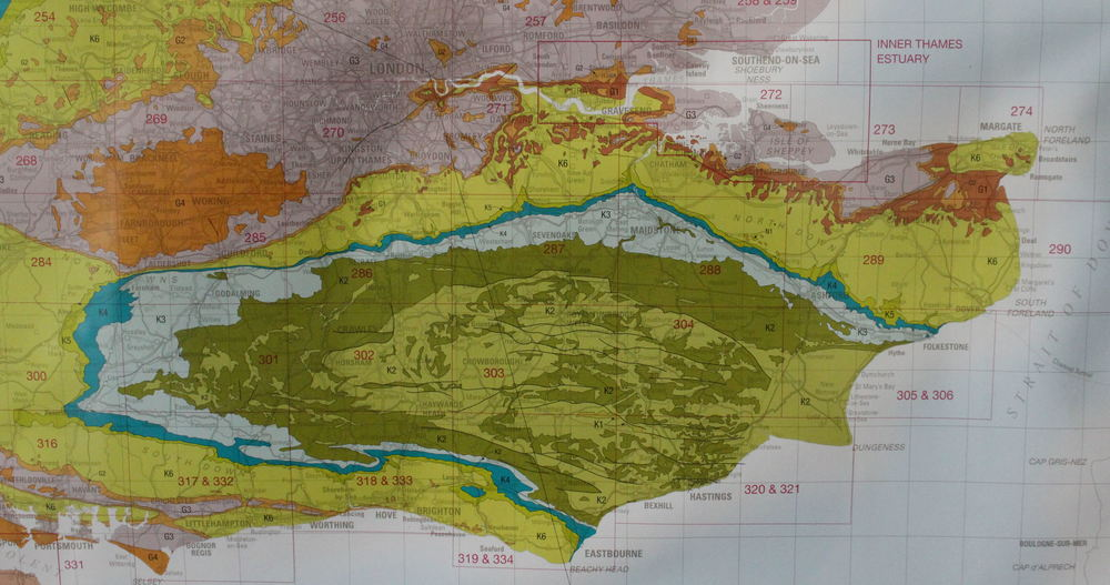 The Greensand Ridge, encircling the Weald of Kent and Sussex, shown in light blue in this terrible photo of a geological map. It's the remainder of a layer of greensand deposit which has been eroded away until just the edges remain; the north and south downs (mustardy-green) are a similar remainder, but of the layer of chalk that was laid above the greensand in the Cretaceous period.
