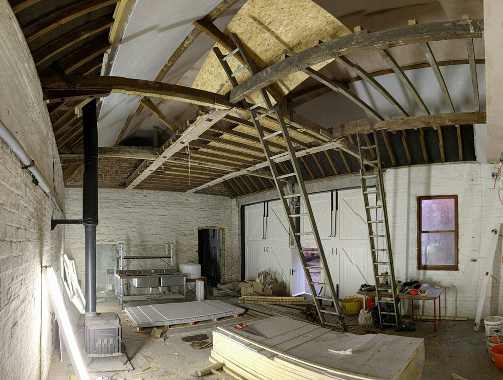 Here is the Warehouse building with much of the ceiling insulation & board in and most of the ceiling boards out. The stove has also gone in and all those beams will keep us warm for at least two years!