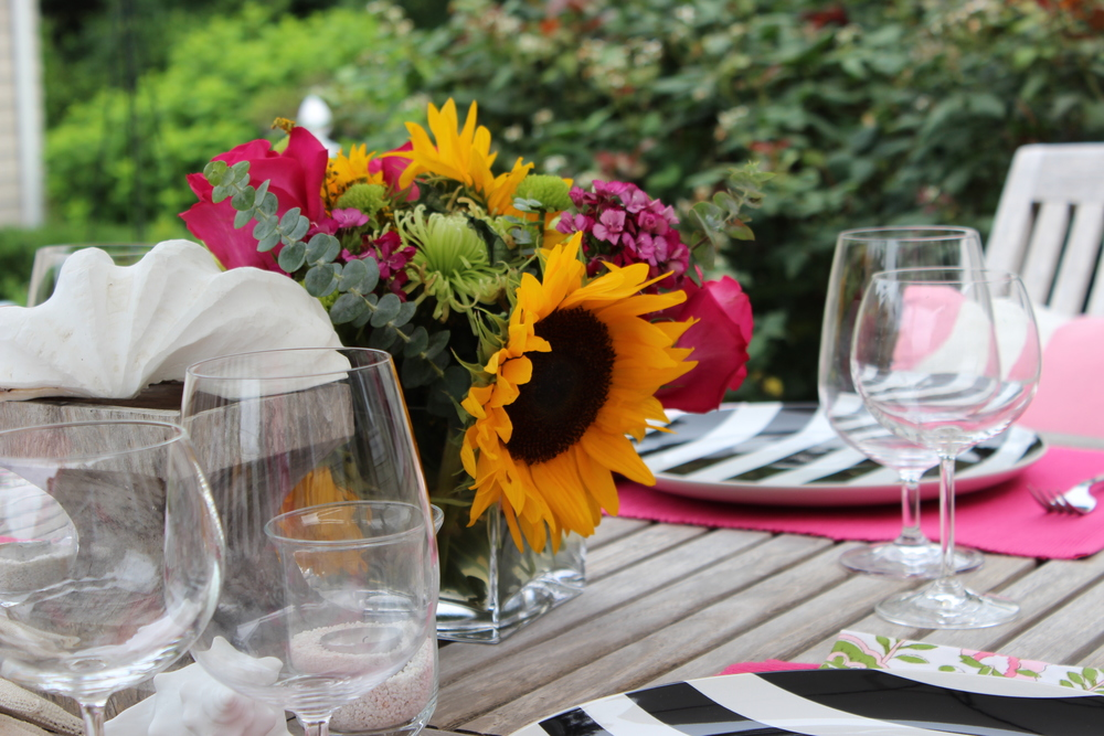 pretty bright black white and pink outdoor dinner table setting with glass and china