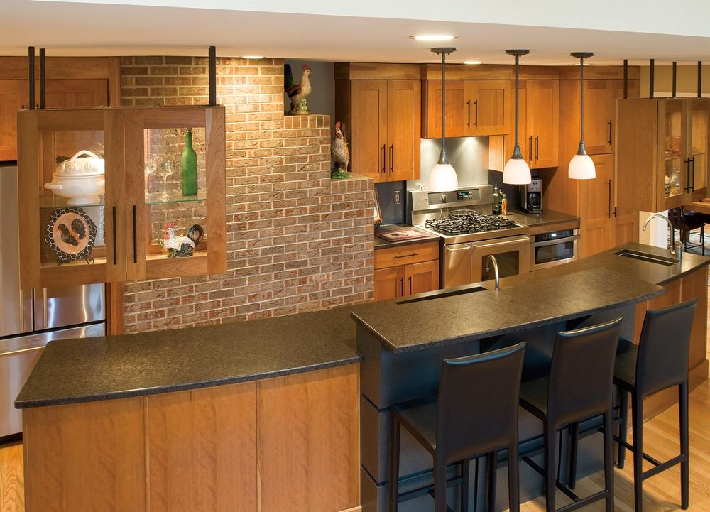 The contemporary kitchen exposes and incorporates the brickwork of the original 1940s fireplace.