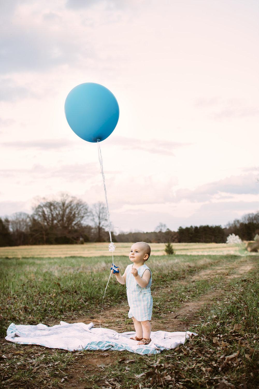 Baby holding large balloon