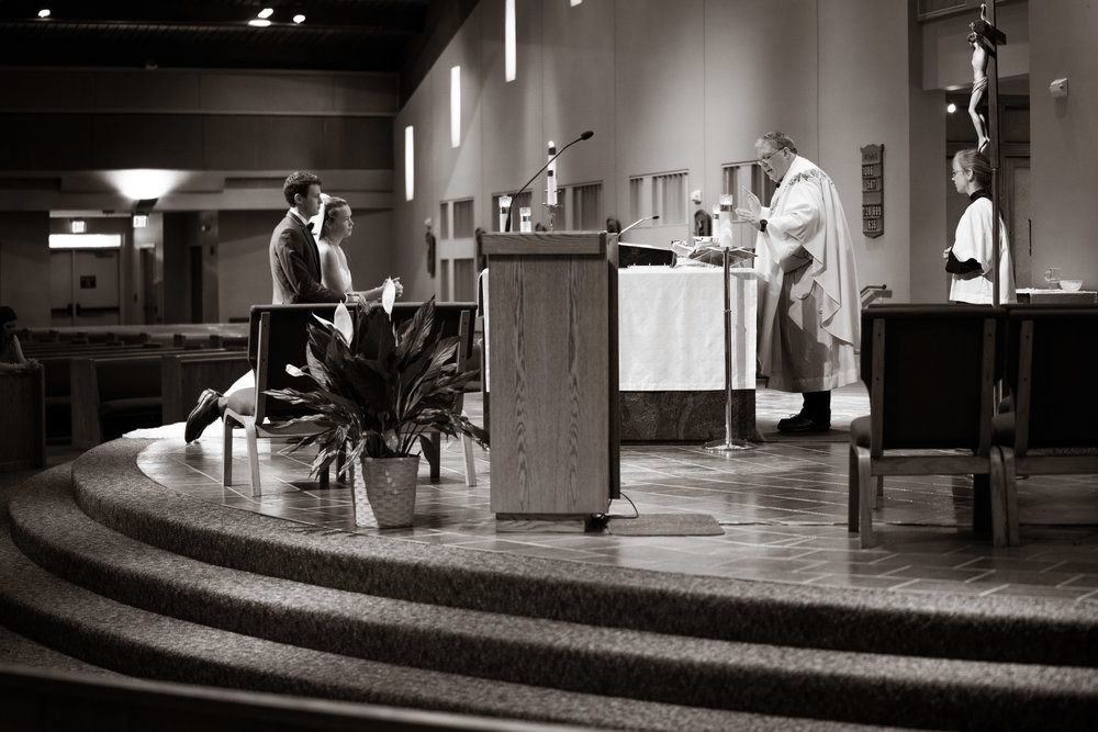 Bride & groom with priest at the alter  | St Mary Magdalene Catholic Church Simpsonville, SC