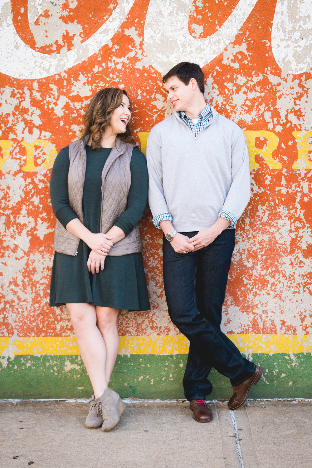 Couple in front of coke sign | Engagement Session Downtown Greenville, SC