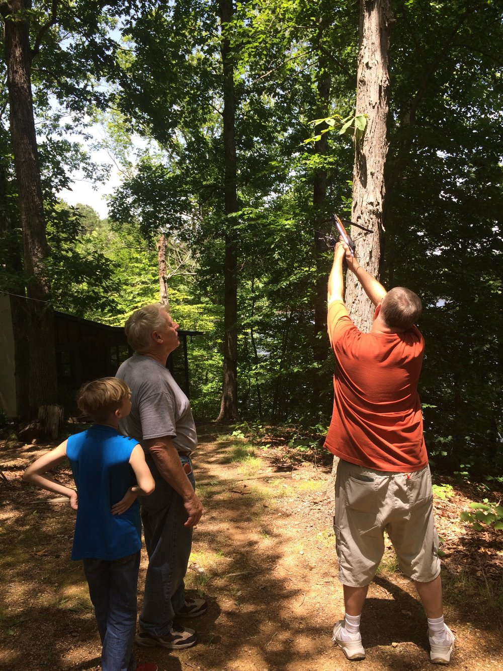 - Ed (WA0YBB), Bill (KG4SAQ) and Ed's grandson Micah continue to launch bolts into the trees to hoist the 40M wire antenna.